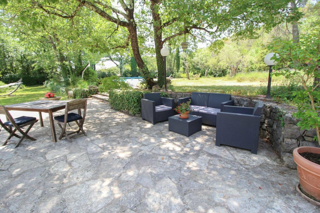 outdoor seaiing area in villa fayence with dark grey couch and large surrounding trees