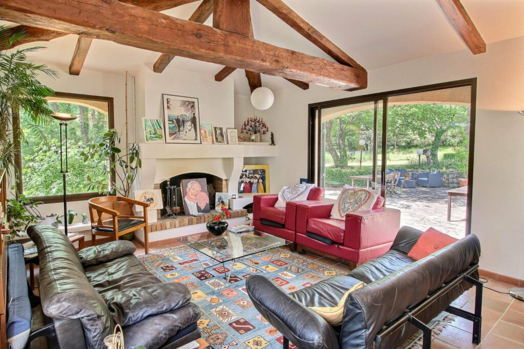 living room in holiday villa with exposed wood beams and large sliding doors red couch and black leather couch