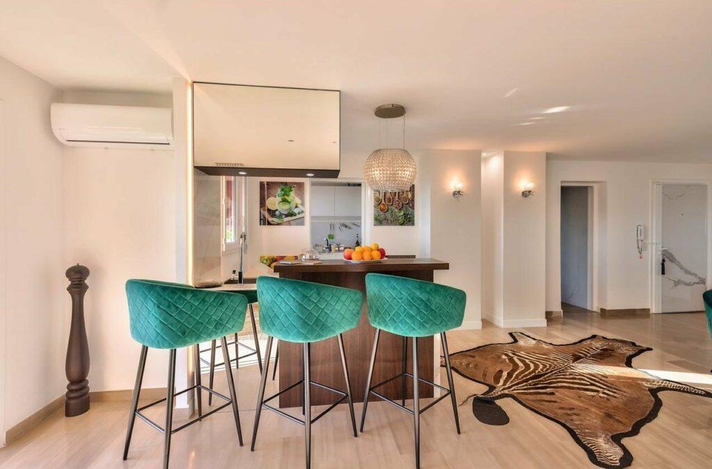 kitchen bar with green velvet stools and modern white light fixtures