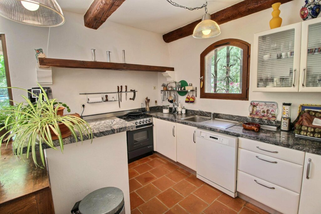 kitchen of provencal villa with white cabinets and granite counter tops with exposed dark wood beams