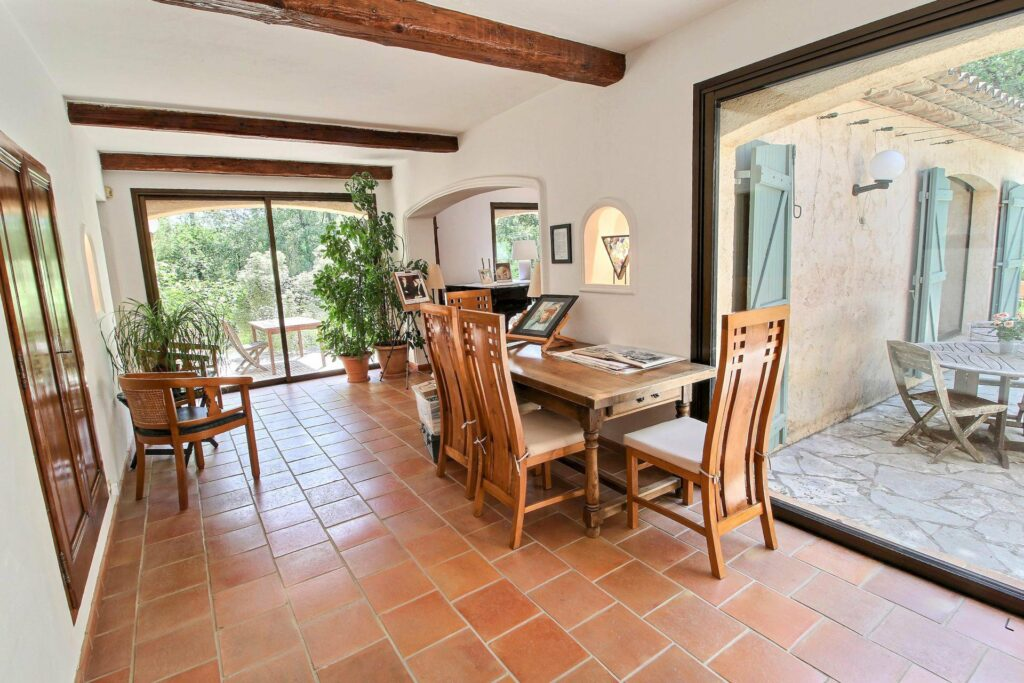 dining room with large wooden table and red toned tile floors andlarge sliding door with exposed wooden beams
