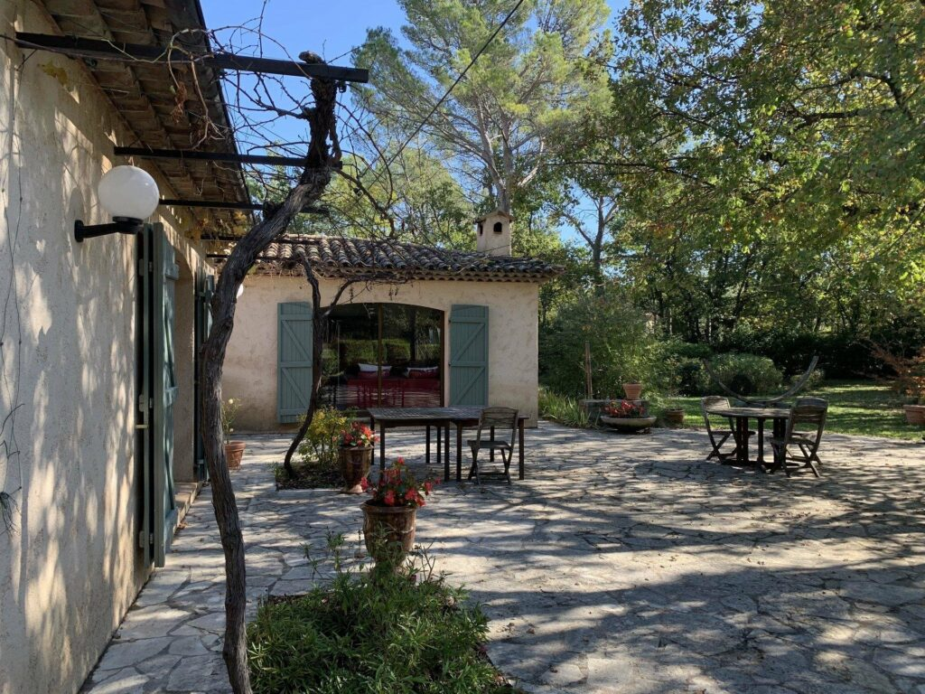 backyard area of provencal villa in fayence for sale with outdoor table and chairs with garden large trees