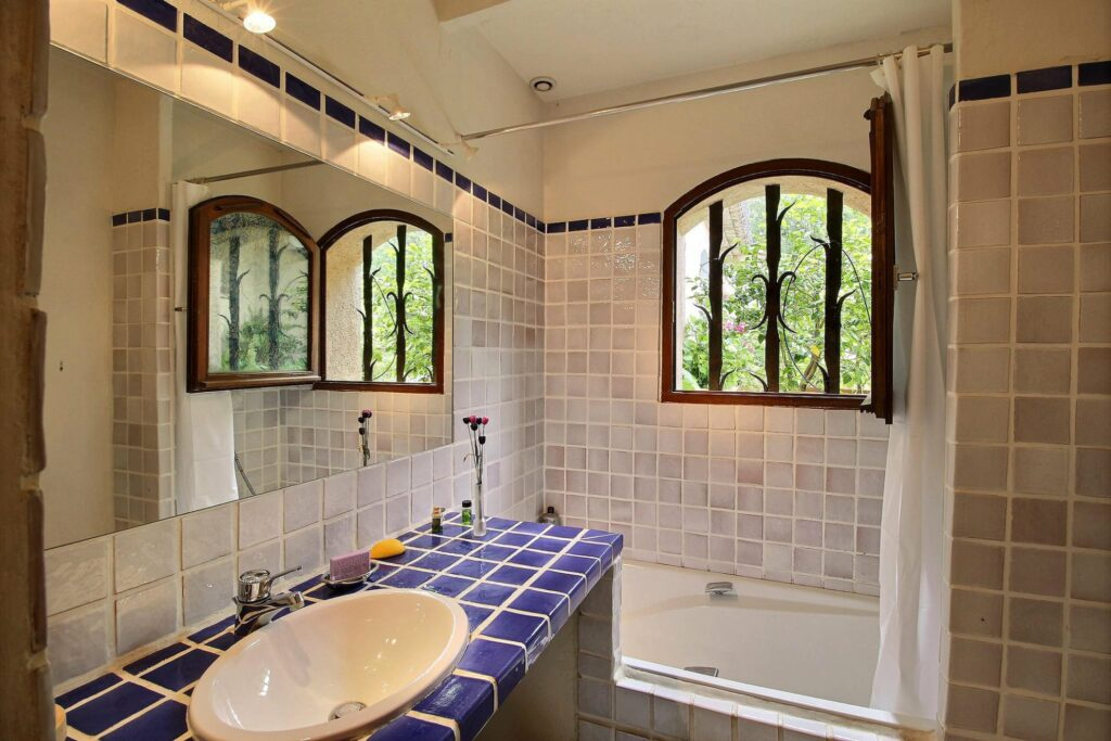 bathroom with rounded windows and white tub tile sink with blue provencal style tile