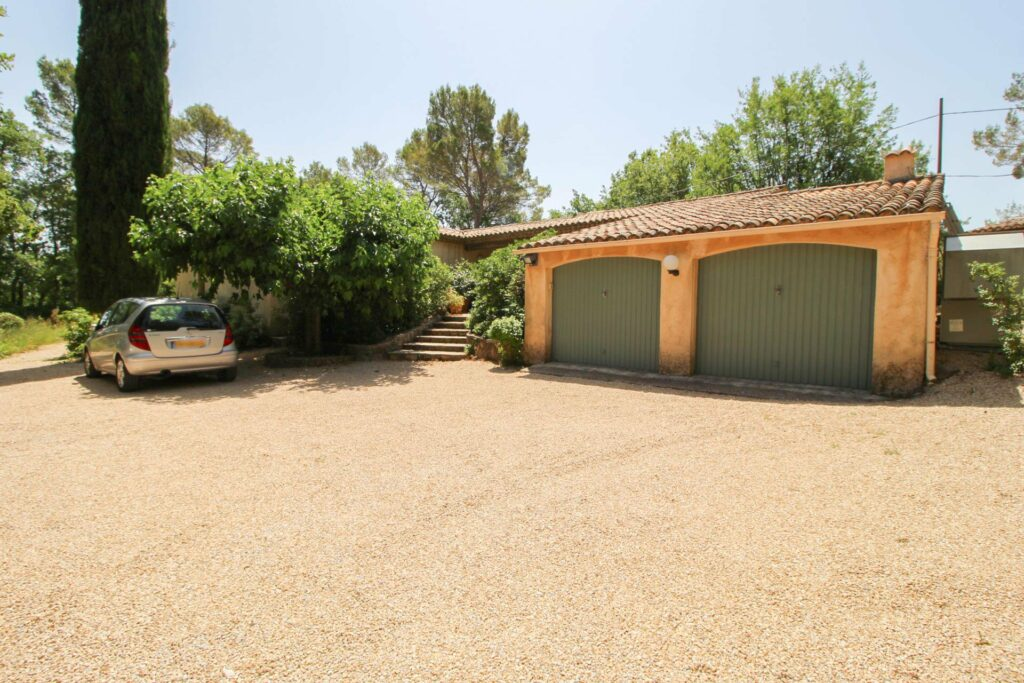 provencal style villa with large two car garage and gravel parking area