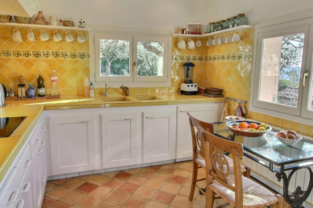 kitchen with white cabinets and bright yellow walls and rustic stone tile floors