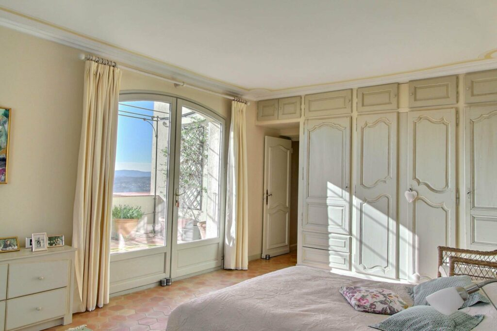 french riviera bedroom with large french doors facing mountain and french cabinets