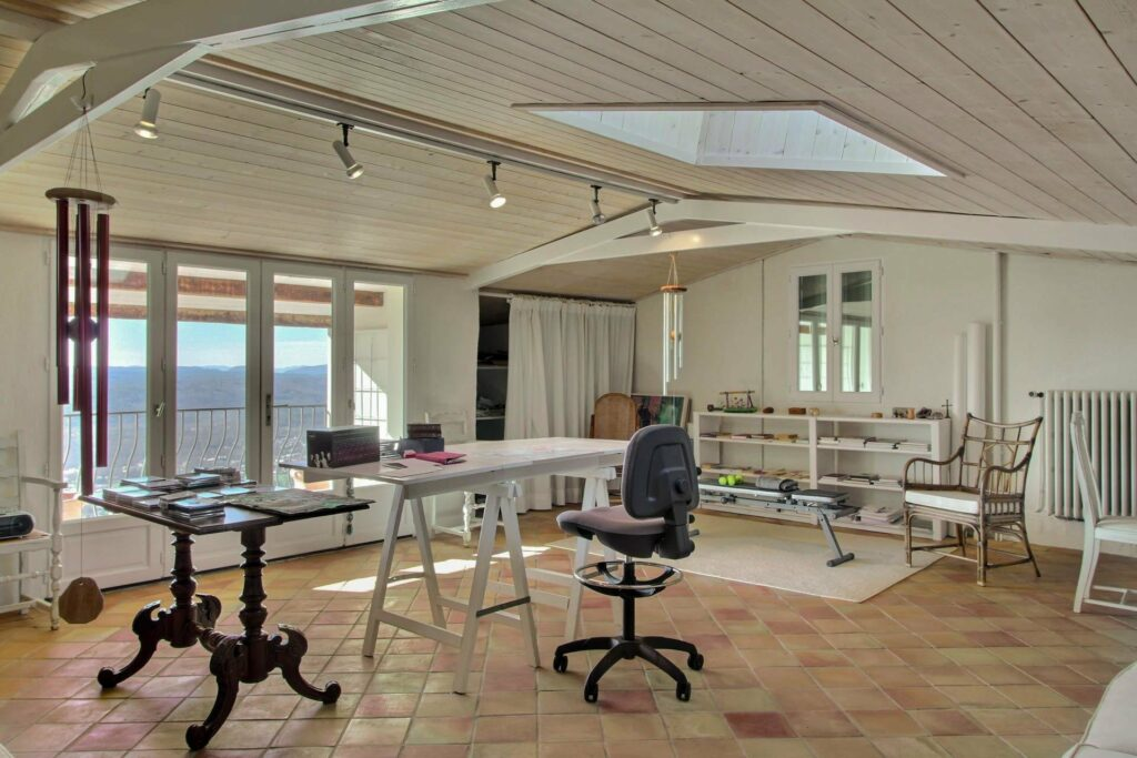 large office space with stone tile floors and skylight with table in center
