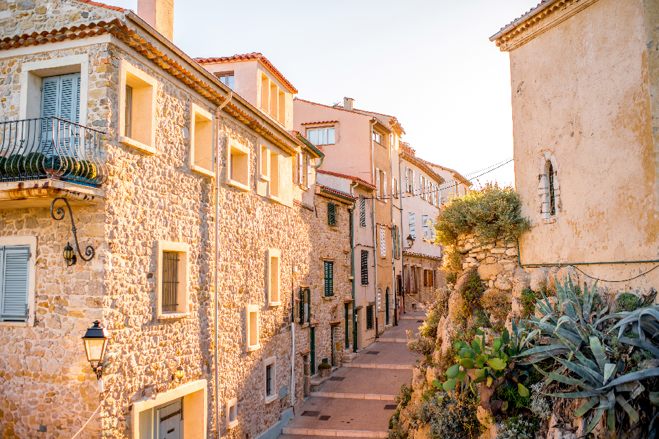 cobblestone streets of Old town in Antibes. Plants growing out of the stone walls. Golden light fills the scene as the sun sets in the South of France.