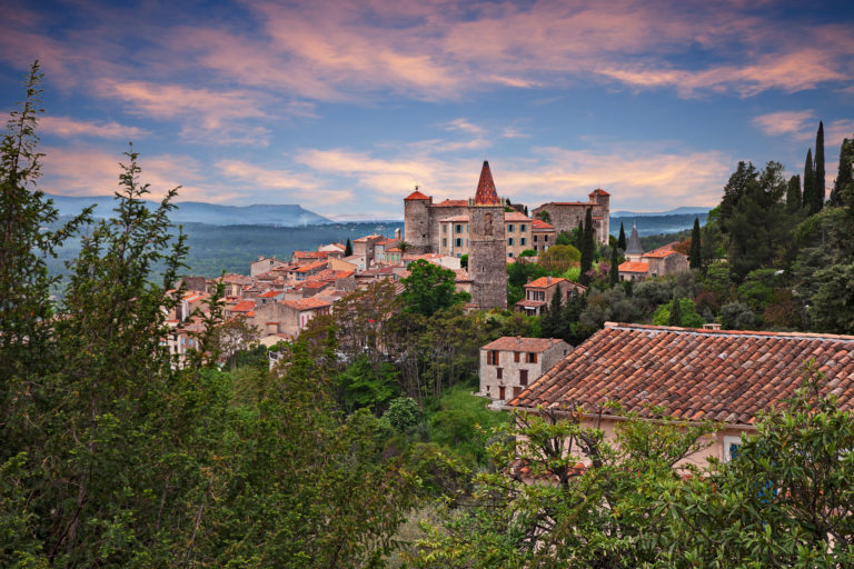 View of a village in Pays de Fayence. Scenic view of the trees and old historic buildings in the South of France.
