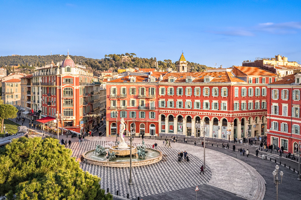 Massena Square in Nice, South of France. Checkered tile floors and a large fountain of Apollo. Surrounding terracotta buildings that cover the streets of the old quarter.