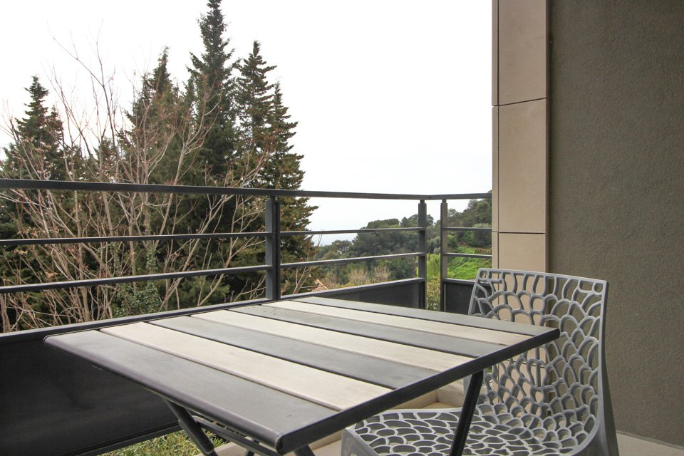 terrace of apartment in eze with small wooden table and view of garden