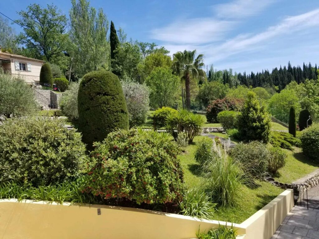 large garden with bright green trees at villa in Grasse