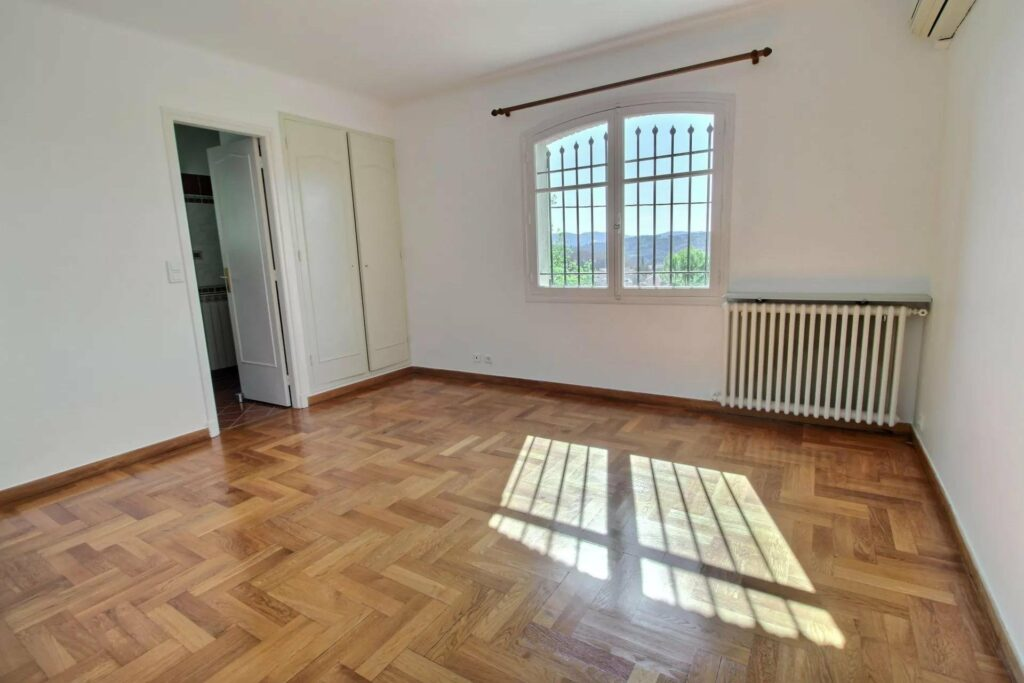 bedroom of grasse villa with light colored wood floors