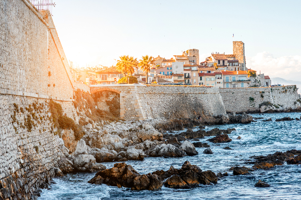 view of the rocky shores of Antibes with the sun setting behind the buildings.