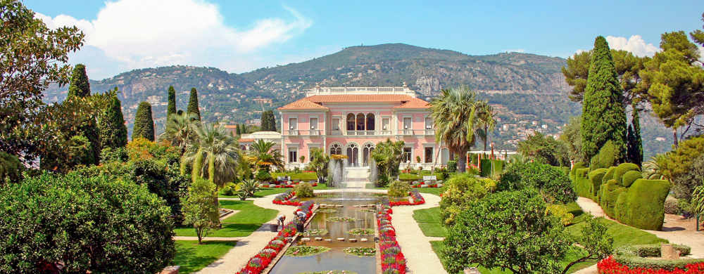 light pink large mansion in south of france. Beautiful garden surrounding private fountain and mountain view in the back.