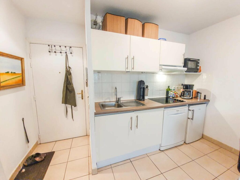 kitchen with white cabinets and tile floors at studio apartment