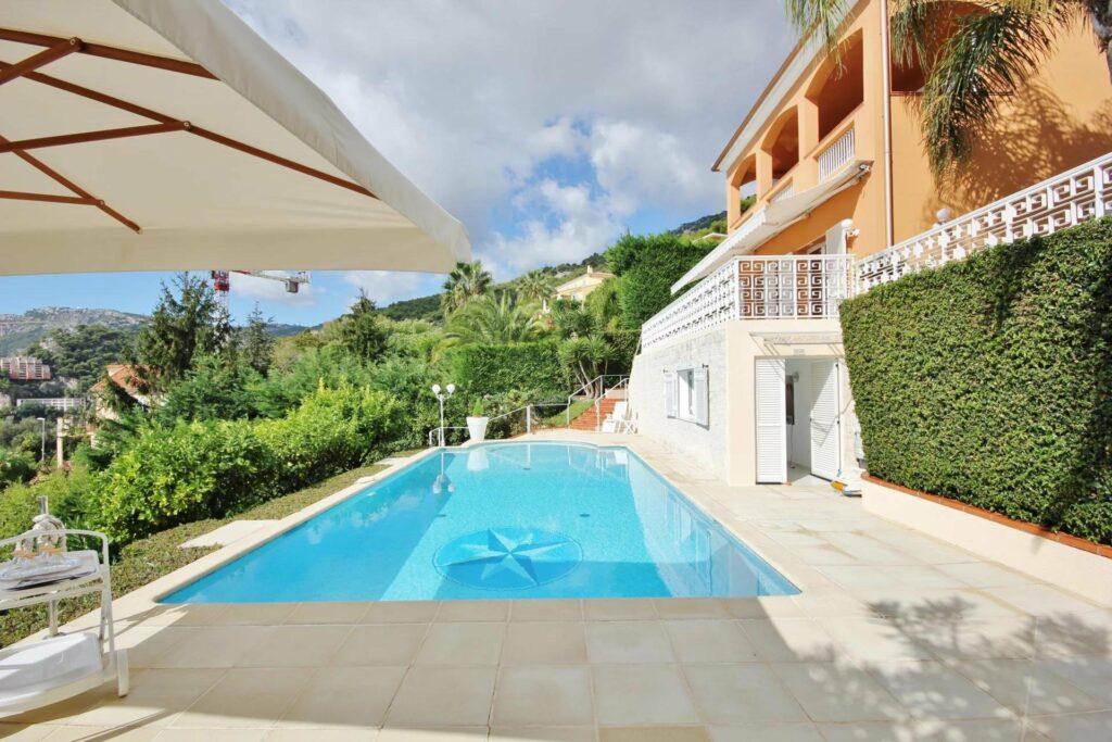backyard of villa with a deep blue pool and greenery wall