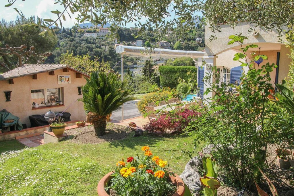 garden with flowers and view of pool at south of france property