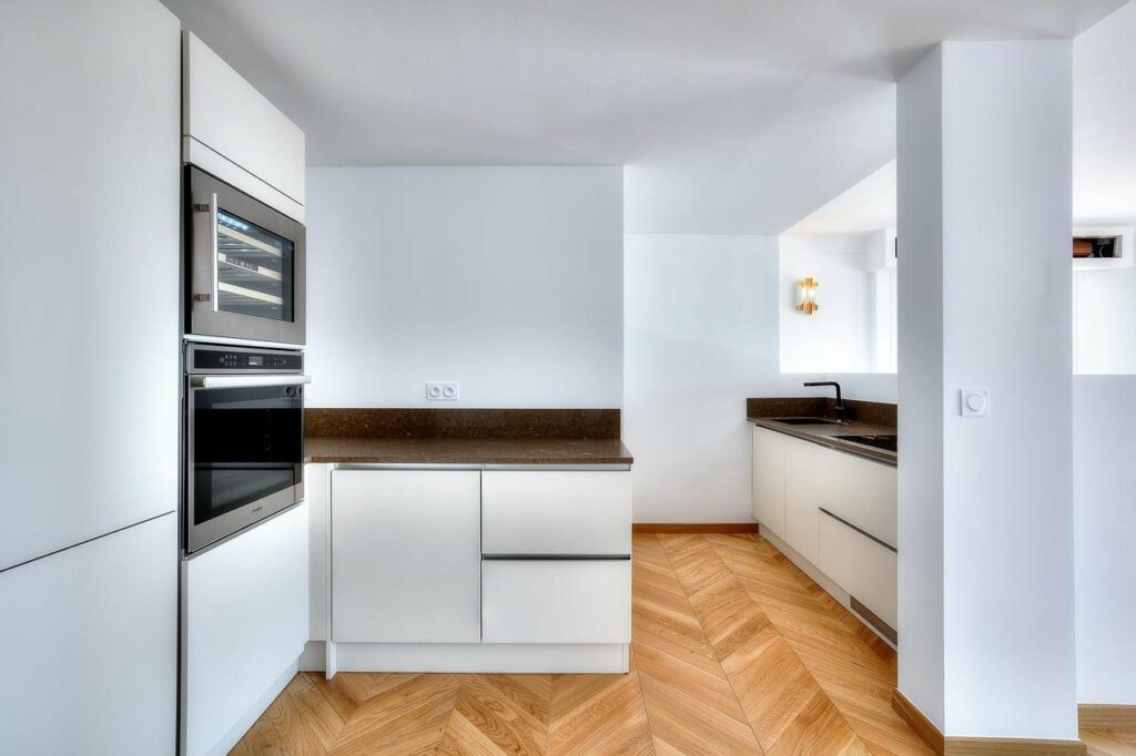 kitchen with white walls and chevron wooden floors with modern appliances