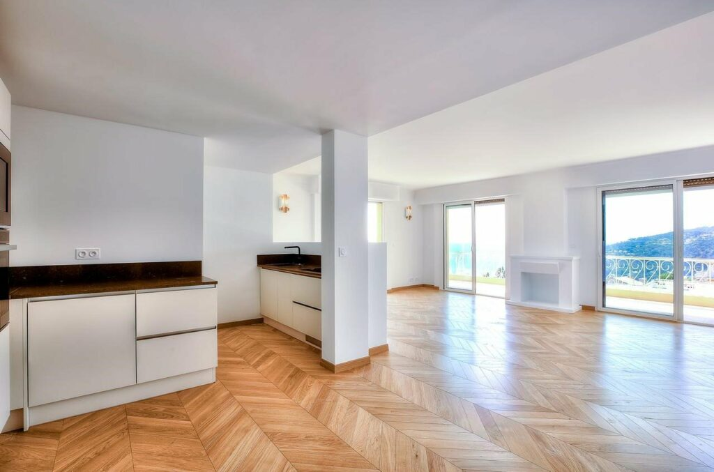living room and kitchen area in apartment with chevron wood floors