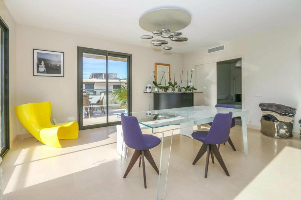 dining room at penthouse apartment in nice for sale with glass table and purple chairs