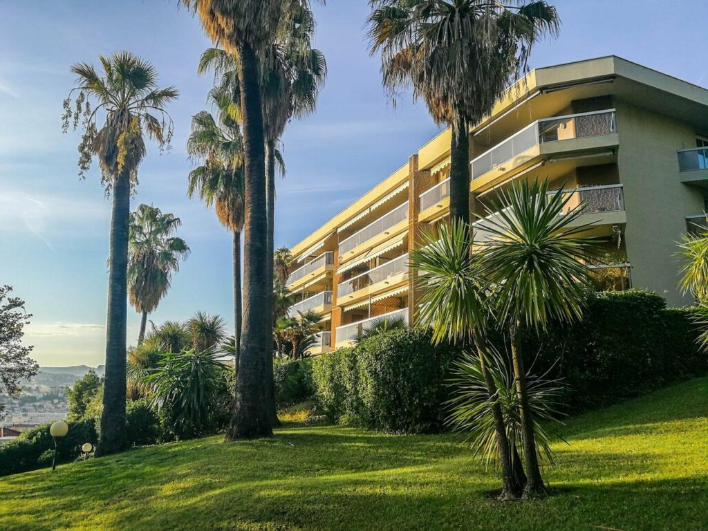 apartment building in south of france with palm trees surrounding it