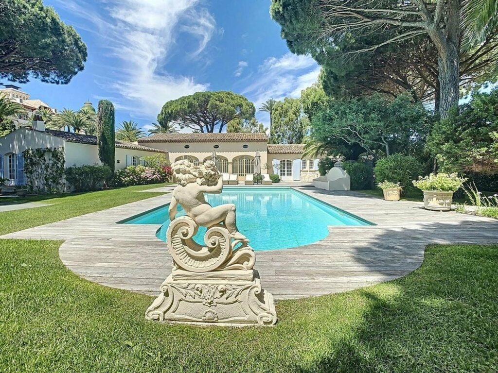 large backyard of villa in saint tropez with long blue pool and white statue