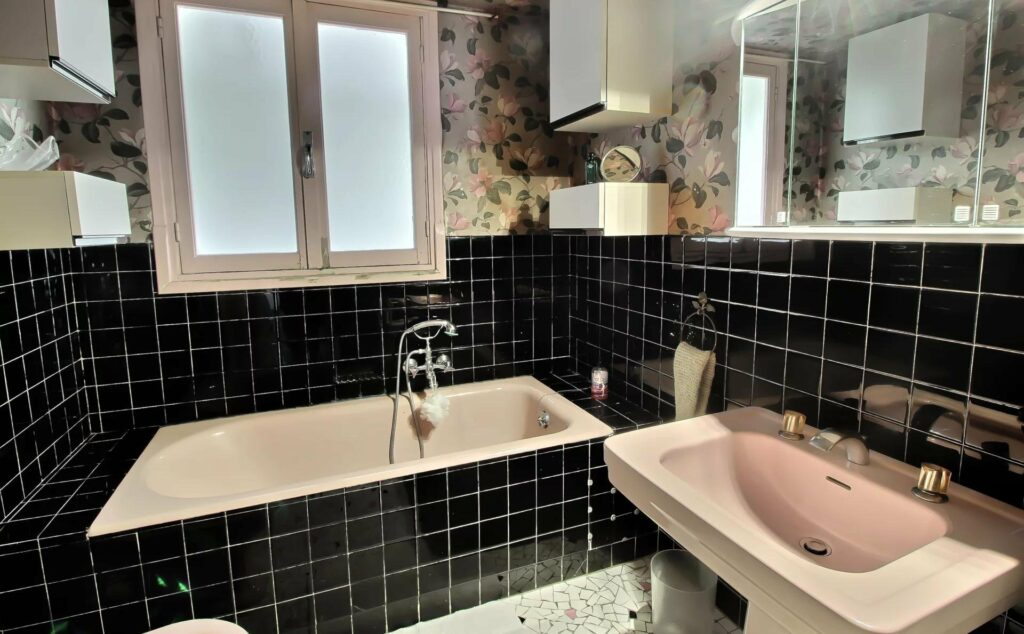 bathroom with a white bathtub and dark tile and a window