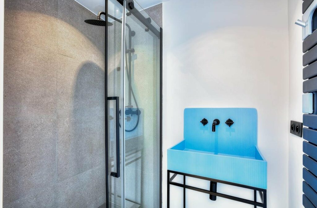 bathroom with blue farm house sink and matte black shower head