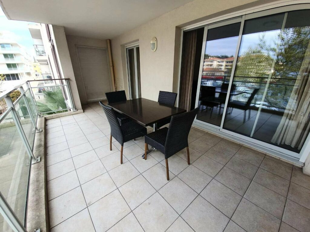 terrace with outdoor chairs and table with tiled floor at central apartment