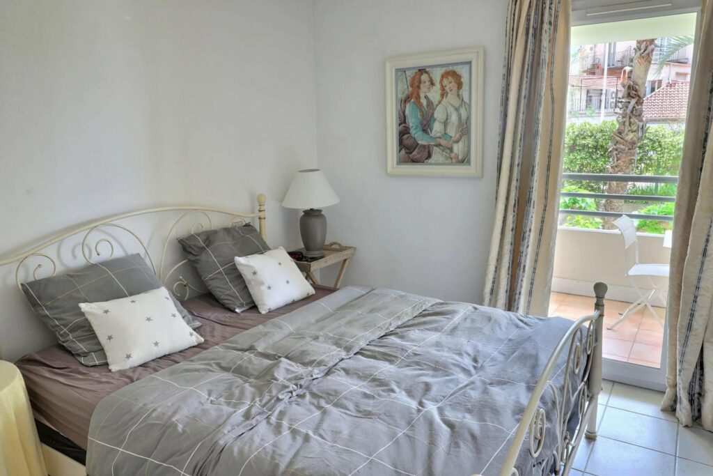 bedroom of apartment in south of france with large window and grey colored bedding