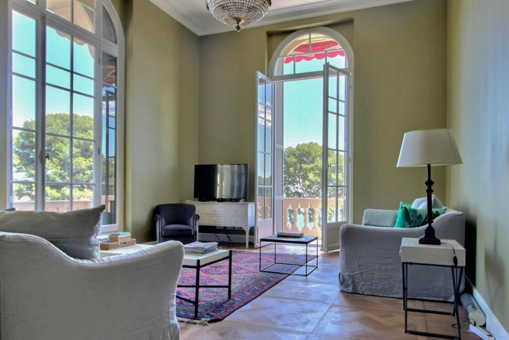 living room at apartment in south france with open french doors to balcony and sage colored walls