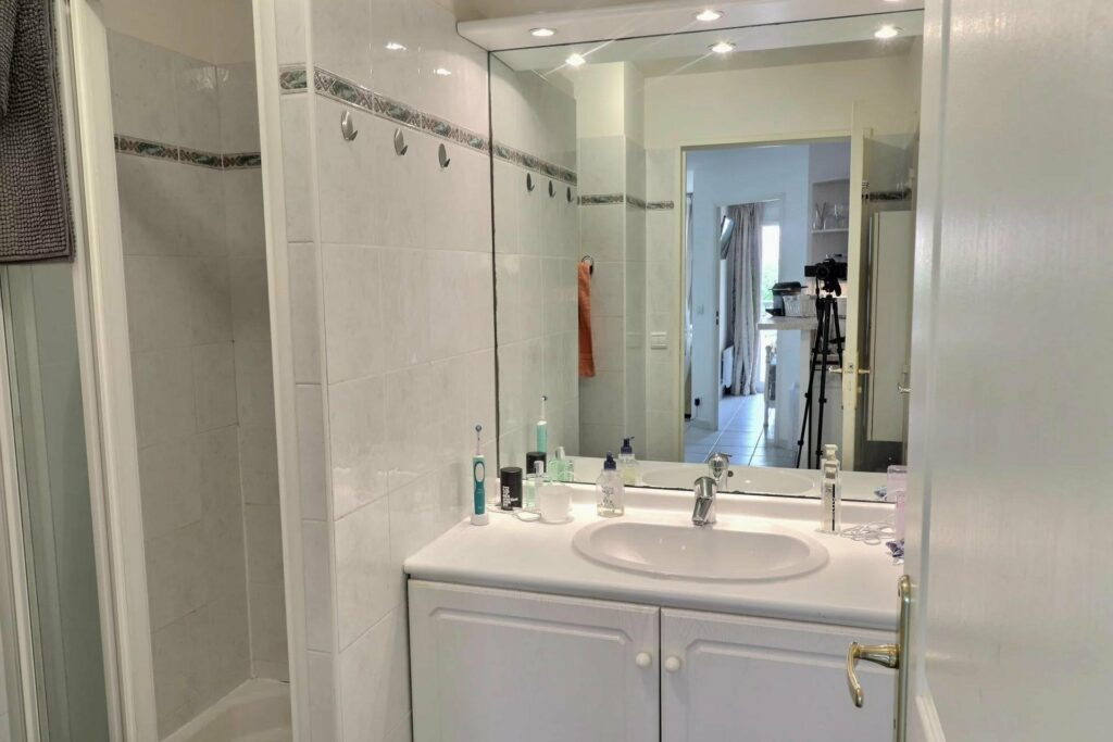 bathroom of apartment in saint raphael with large glass window and white cabinets