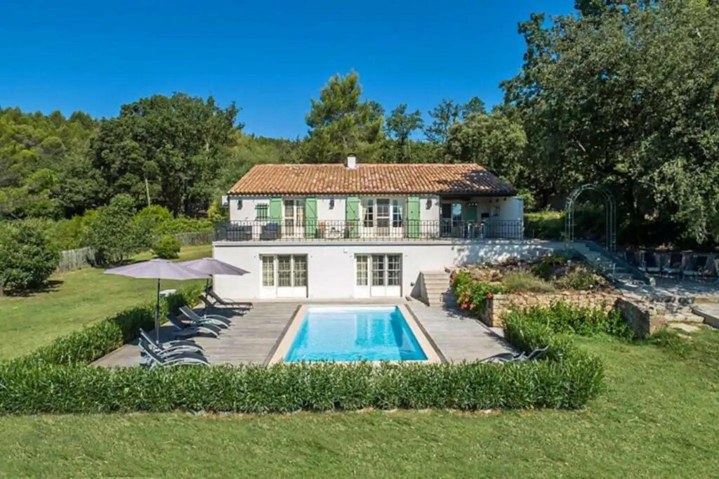 villa and pool with garden and pool chairs