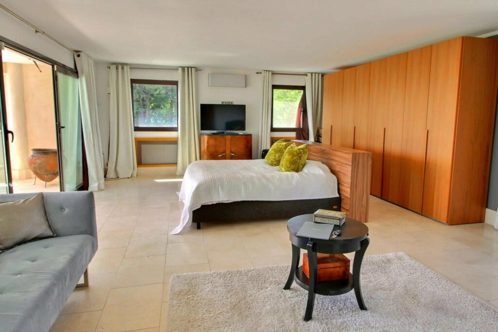 bedroom at luxury villa with stone tile floors and bed in center with green accent pillows