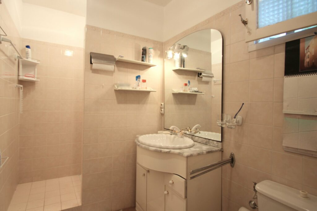 small bathroom with single sink and mirror with white walls