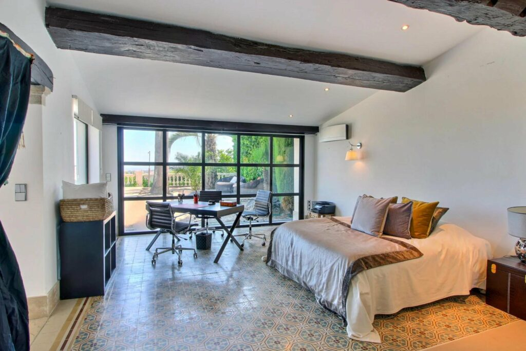 bedroom wih pattern tile floors and exposed dark wood beams with large comfortable bed and glass wall with access to balcony