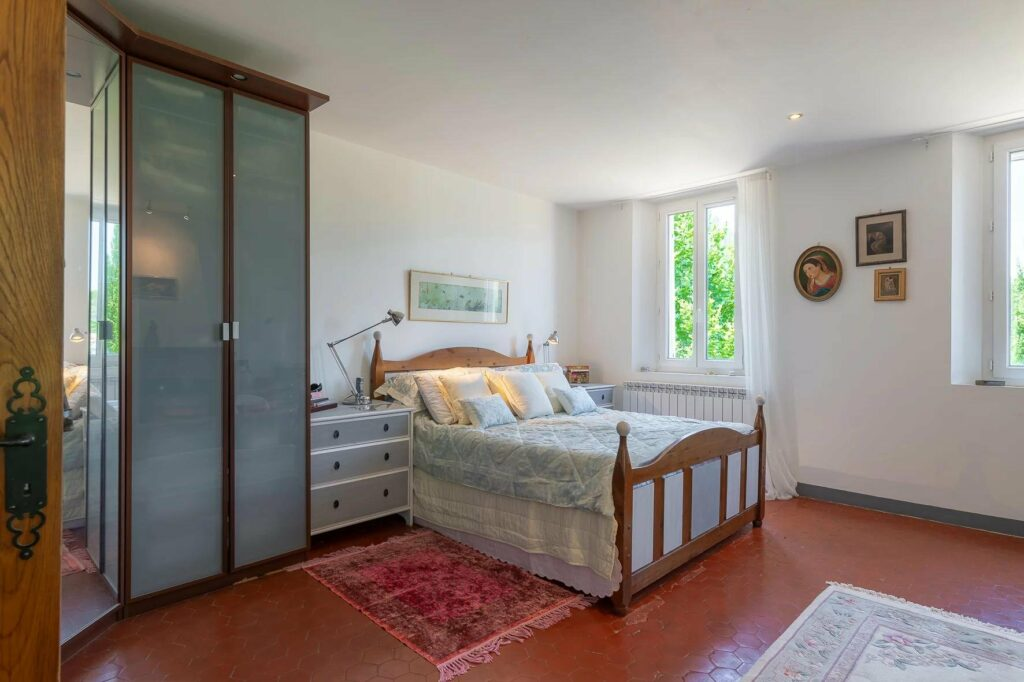 bedroom of villa in south france with double bed and small window facing garden