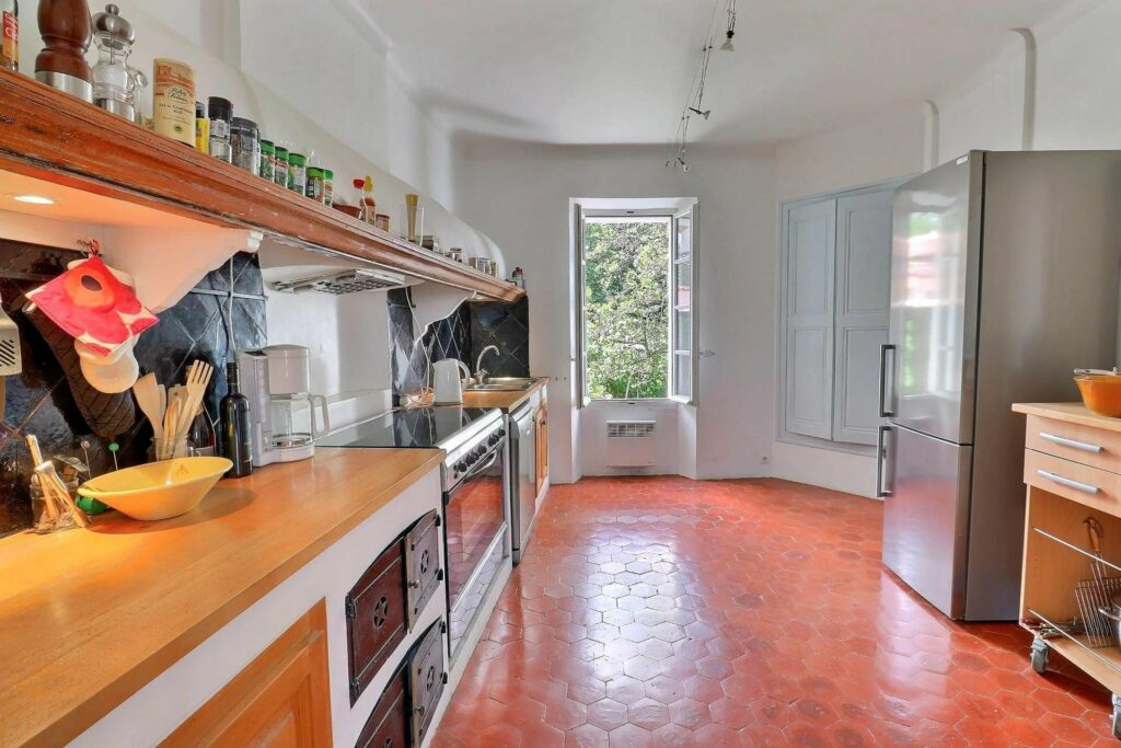 kitchen with red toned wooden floors and light wood cabinets and large windows with garden view