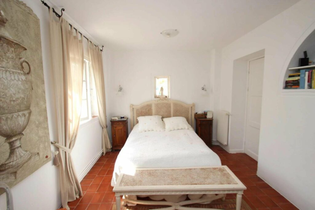 bedroom with bed in center and rust colored tile floors