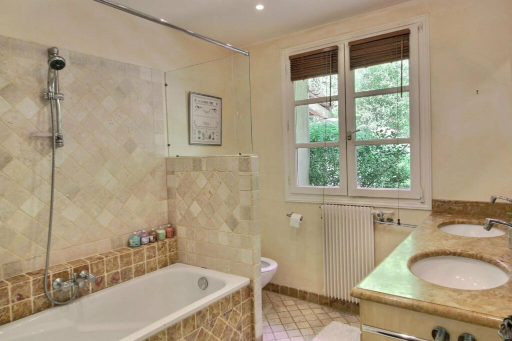 bathroom of house with bath tub and standing shower and light pebbled tile