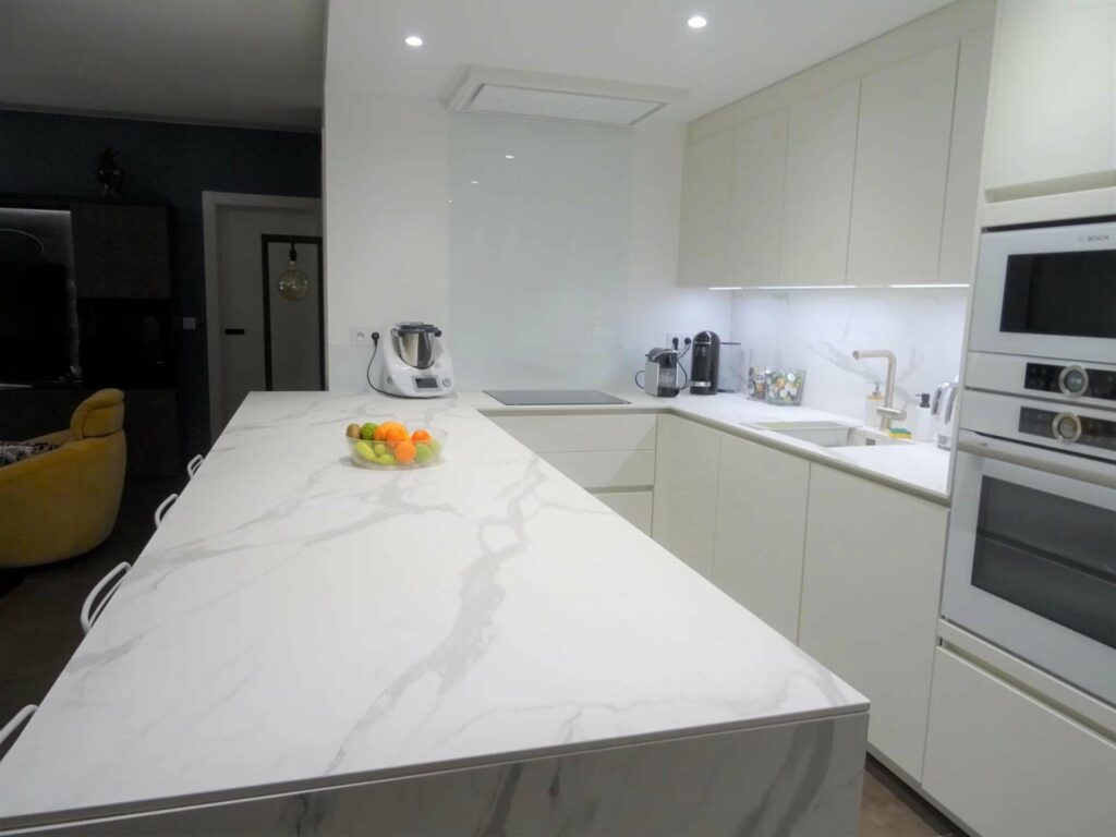 large white marble kitchen top island with white surrounding cabinets