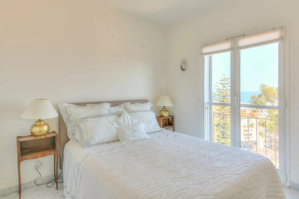 bright white bedroom with city and sea view in south france