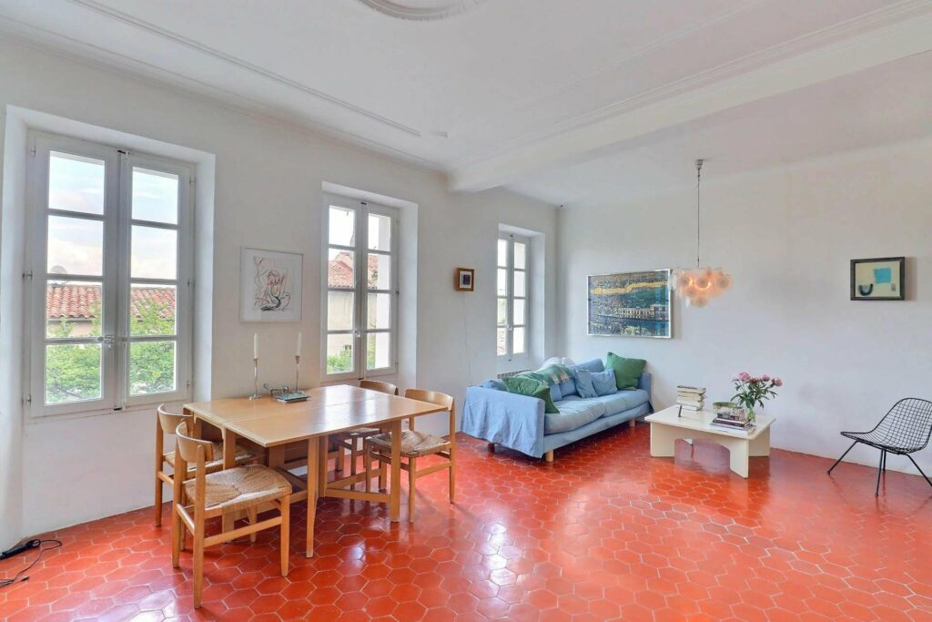 living room of apartment in south france with red toned wood floors and blue coach in center with wooden dining table