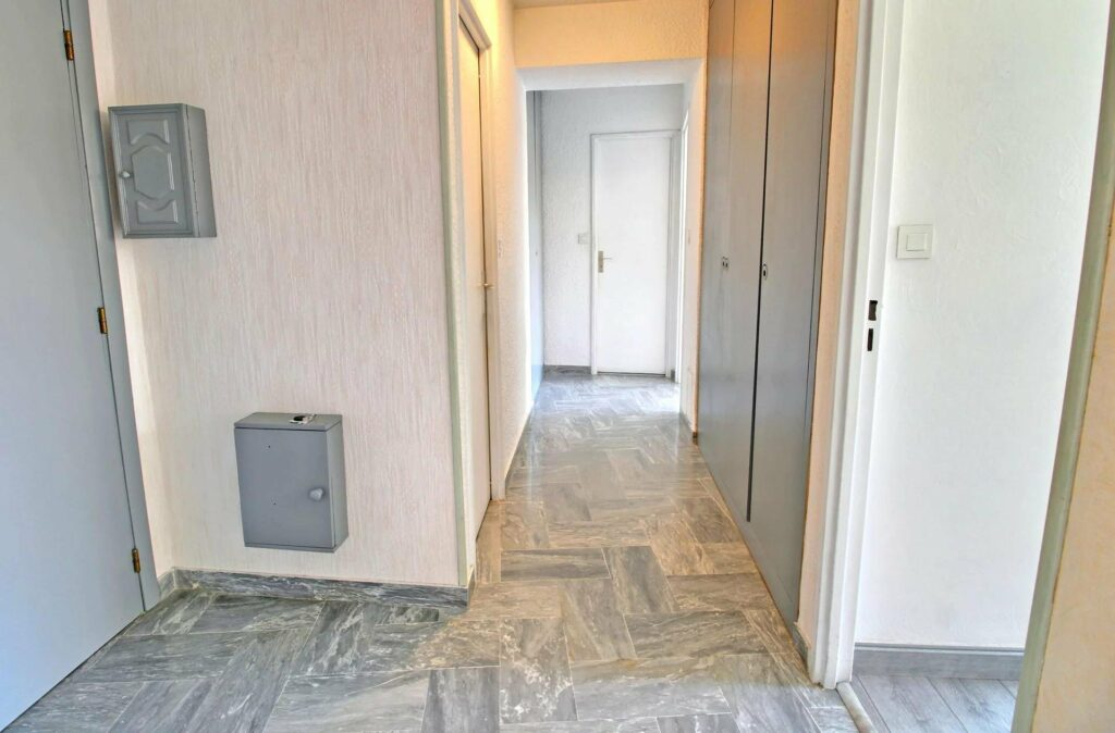 hallway with grey tile floors and white walls