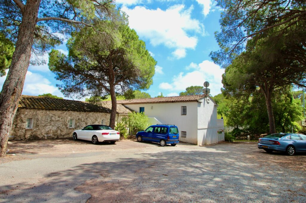 parking area with stone wall and center tree of apartment for sale in st. raphael south freance