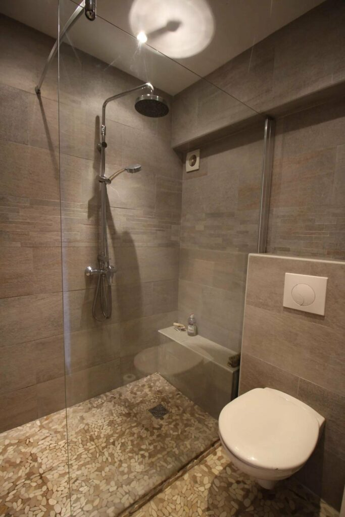 modern style open bathroom with grey tile standing shower and white floating toilet