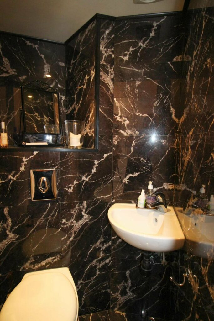 modern apartment bathroom with dark marble walls and white sink