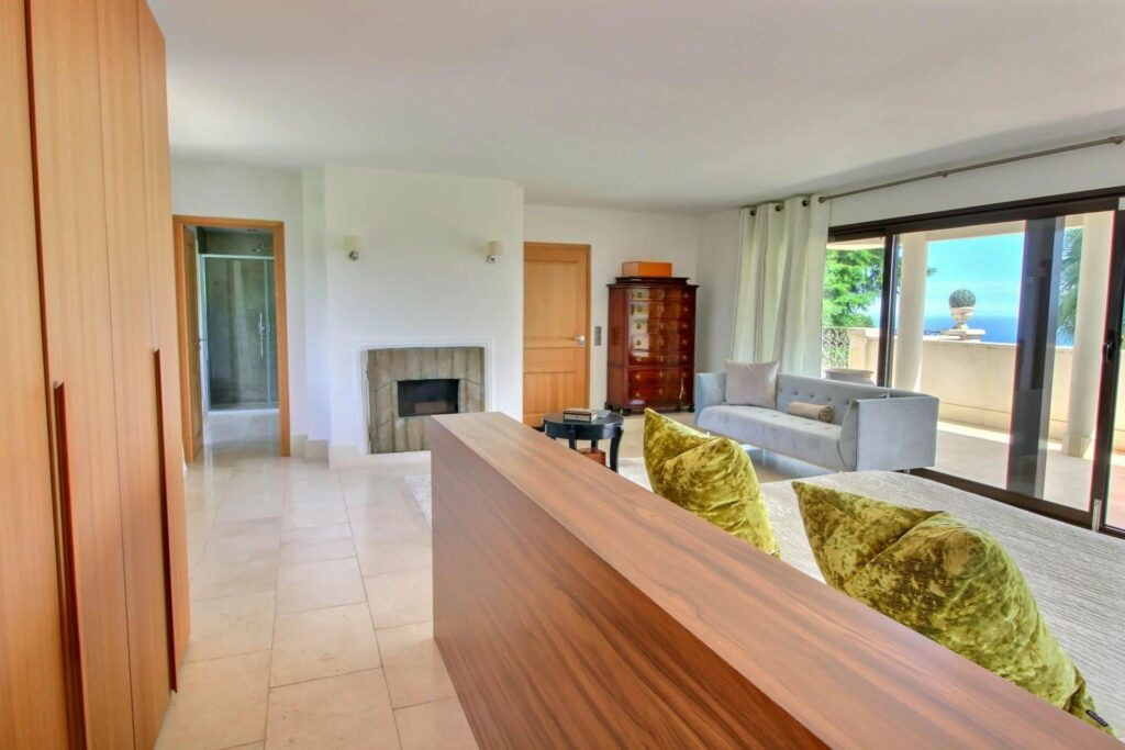 modern large bedroom with tile floors and fireplace with large glass sliding door with sea view