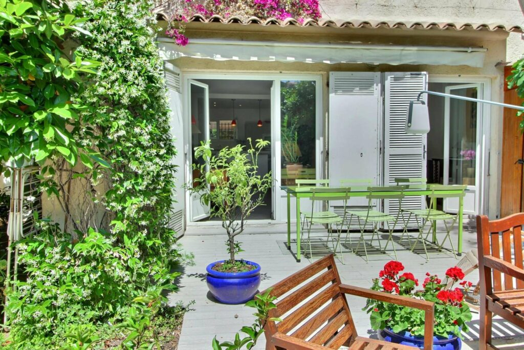 backyard of apartment for sale in villefranche with greenery and tiling wooden outdoor furniture